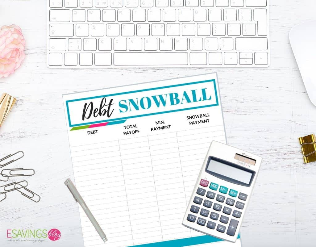 Printable Debt Snowball Tracker on desk. Used to help pay off debt and do a zero based budget.